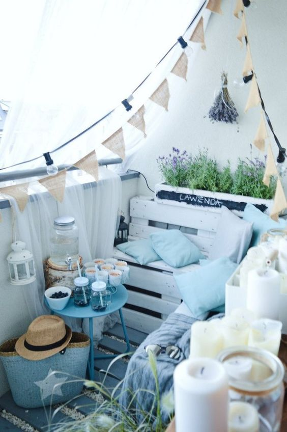 a summer balcony with a pallet corner bench, a blue table, some tulle and buntings, lights and lavender feels like Provence