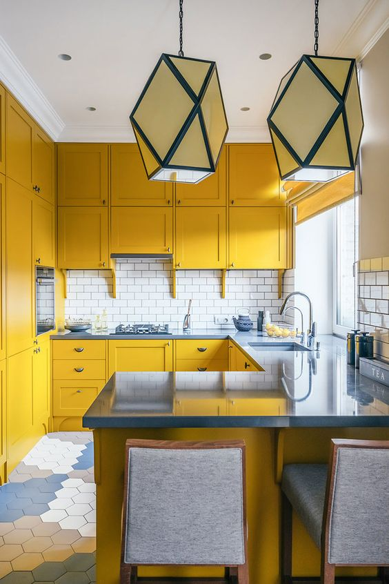 a sunny yellow kitchen with blue countertops, a white subway tile backsplash and catchy geometric pendant lamps