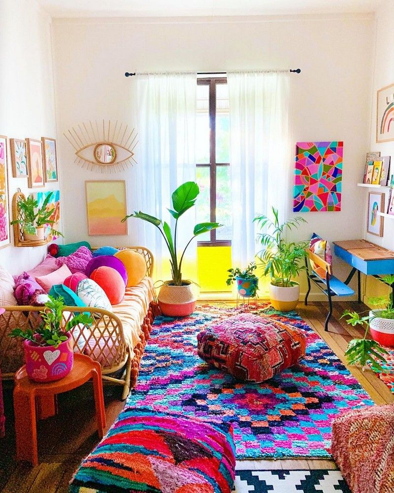 a super bright boho living room with a rattan sofa, very vibrant textiles and tassels, potted plants and a bold gallery wall