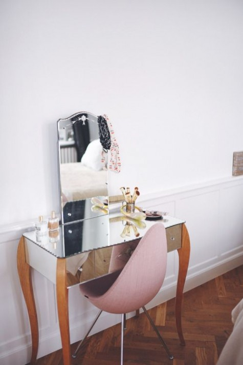 a tiny and cozy makeup space with a unique mirrored vanity with wooden legs and a pink egg shaped chair