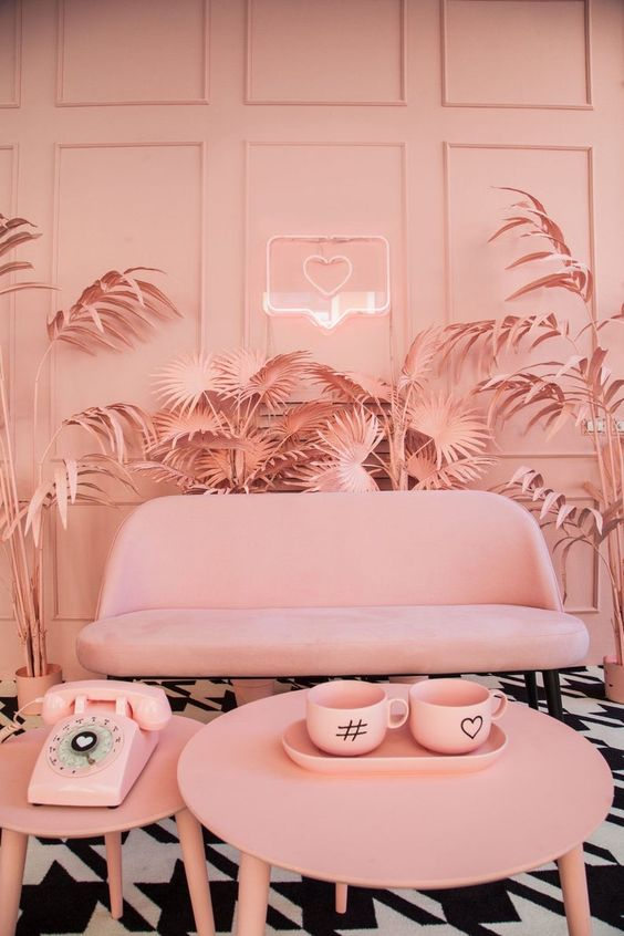 a total candy pink living room with fun modern furniture and a pink neon sign that adds light to the space
