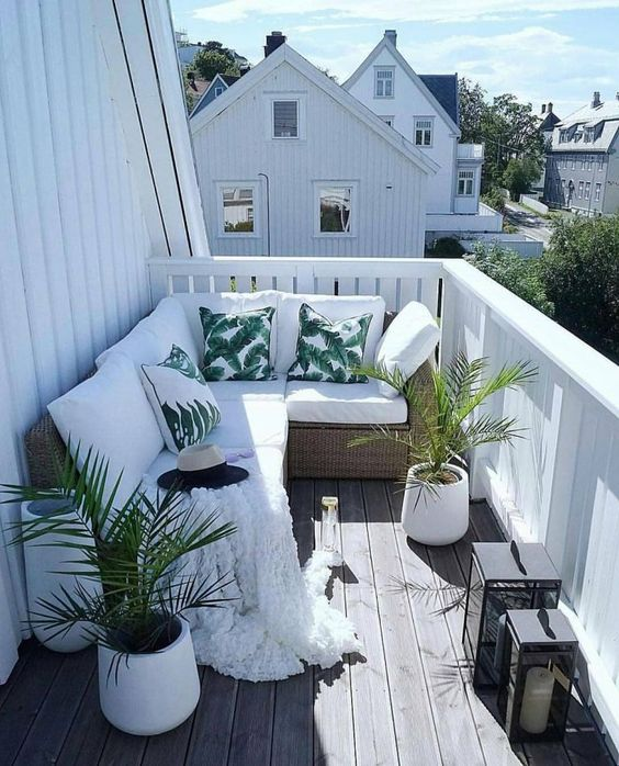 a tropical balcony with a corner bench, potted plants, tropical print pillows, candle lanterns is small yet welcoming