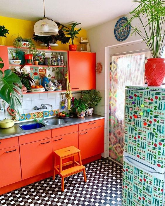 a vibrant kitchen with a yellow wall, coral red cabinets, a floral print fridge and a checked floor is very fun and lively