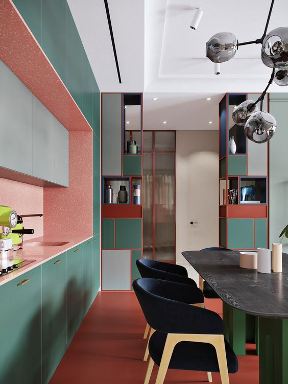 a vibrant kitchen with green, pink and grey cabinets, with a red floor, green and red storage units and a green table
