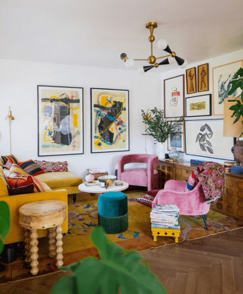a vibrant living room with a yellow sectional, pink chairs, a bold gallery wlal, a colorful rug and potted plants
