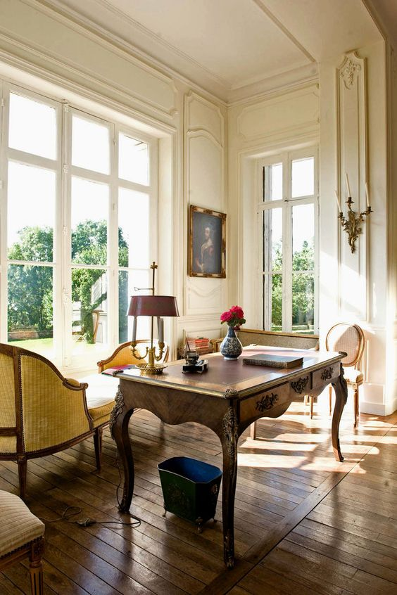 a vintage artwork, a vintage desk and refined chairs, a table lamp and a candleholder on the wall for a more refined feel