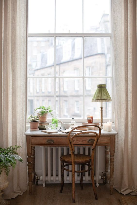 a vintage stained wood desk and a matching chair and a green table lamp, potted plants and a gorgeous view