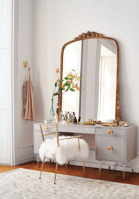 a vintage-styled makeup nook with an exquisite mirror in a refined gold frame, a large grey vanity and a faux fur chair