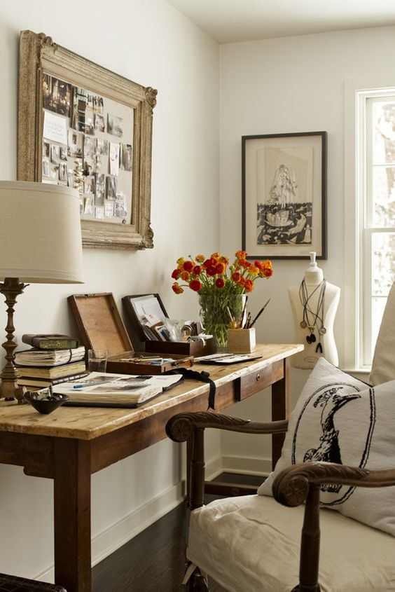 a vintage wooden table used as a desk, a vintage chair with neutral upholstery, beautiful artworks and a table lamp