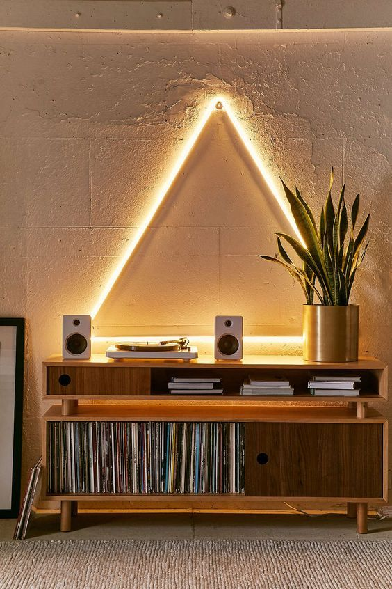 a vinyl playing space highlighted with a neon triangle looks cool and bold and welcomes to play something