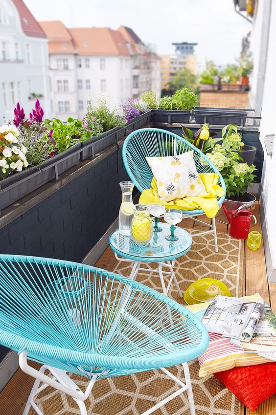 a vivacious summer balcony with blue furniture, colorful pillows and textiles and some poted blooms is welcoming