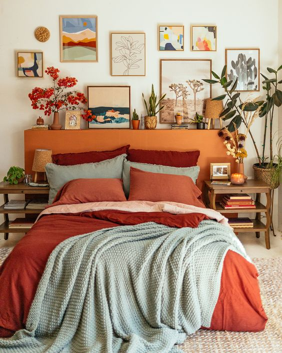 a welcoming and colorful mid century modern bedroom with a rust colored headboard, a colorful gallery wall, bright bedding and some pretty plants