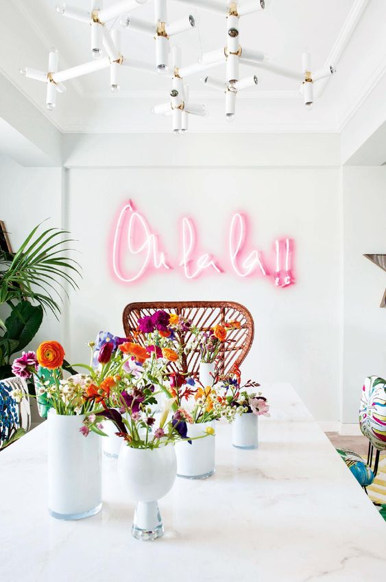 a welcoming dining space with floral chairs, a rattan one, a bright pink neon sign to add a cheerful touch