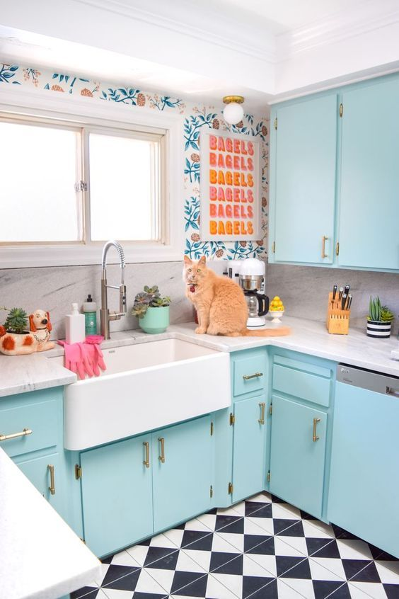 a welcoming kitchen with floral wallpaper, light blue cabinets, a checked tile floor and a bright poster is a cool retro space