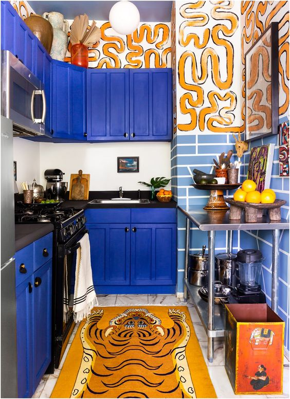 a whimsical kitchen with bold electric blue cabinets, black countertops, painted walls and a faux animal skin rug