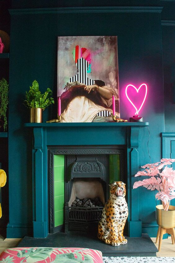 a whimsical living room with teal walls, a non-working fireplace, a bold artwork and a pink heart neon sign on the mantel