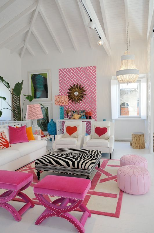 a whimsy living room done with hot pink stools and light pink poufs, a colorful pillows, a pink wall mural and bright lamps