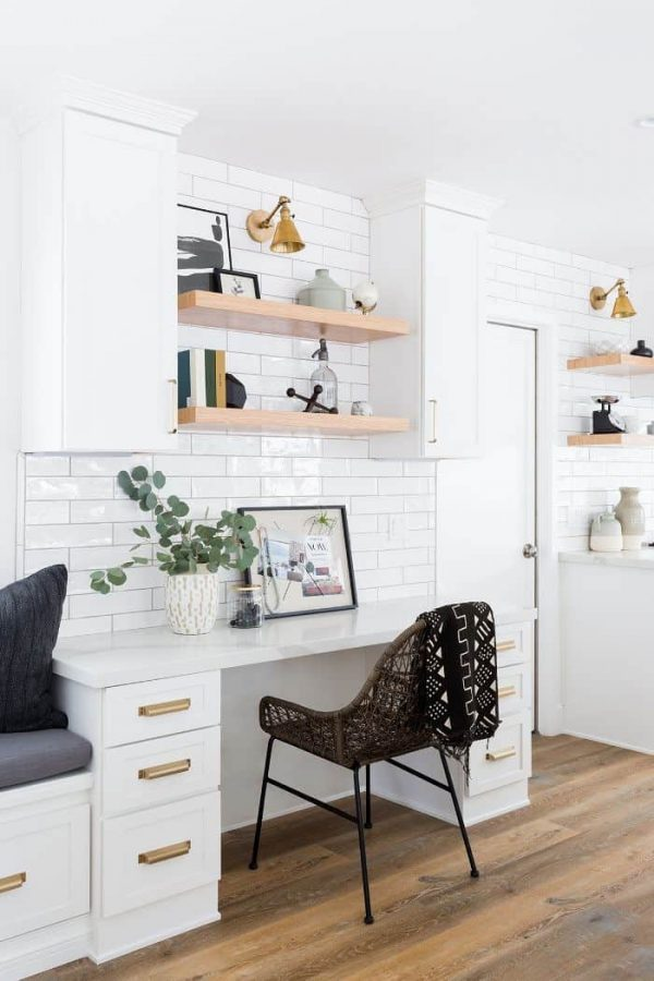 a white farmhouse kitchen with cabinets and a desk that match, with floating and built-in shelves and a cool rattan chair
