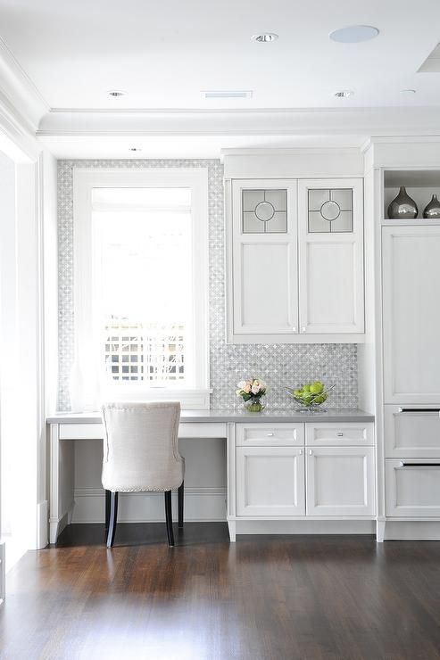 a white farmhouse kitchen with shaker cabinets and a built in desk, a grey countertop and a chic chair   this space can be used for having breakfast