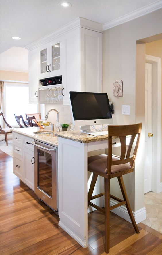 a white farmhouse kitchen with stone coutnertops and a raised countertop plus a tall stool that form a working space right here