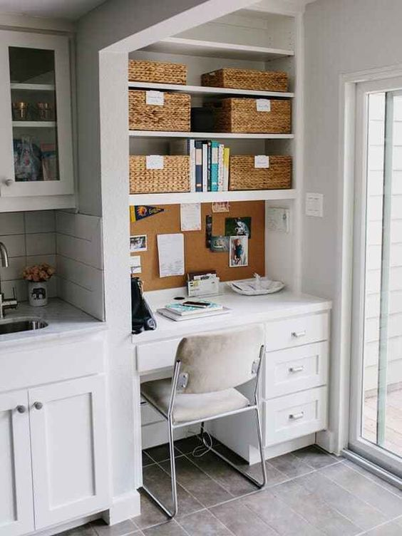 a white farmhouse kitchen with white subway tiles and a stone countertop plus a matching desk and shelves by the window plus baskets