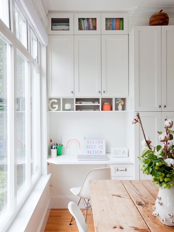 a white shaker style kitchen with a built in matching desk, a cabinet over it and a white chair plus some open shelves