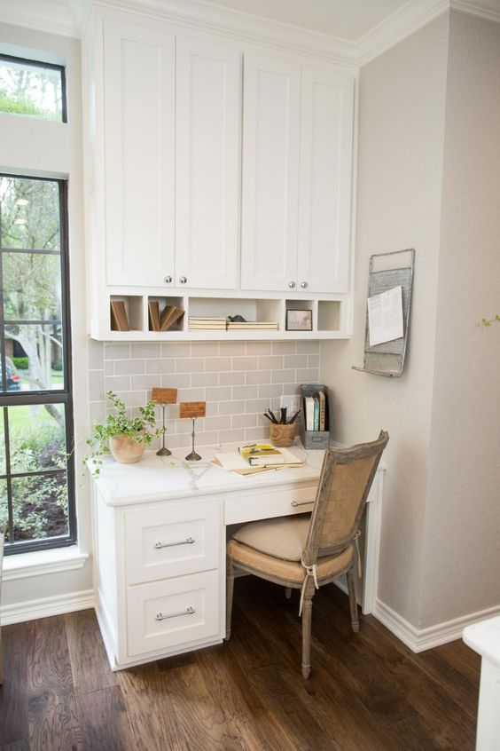 a white shaker style kitchen with grey tiles and a desk plus a cabinet over it and a vintage chair for a working space by the window