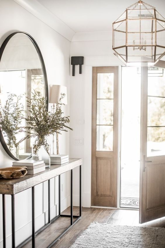 an airy modern entryway with a rough wooden console table, a large round mirror, a faceted pendant lamp and a simple rug