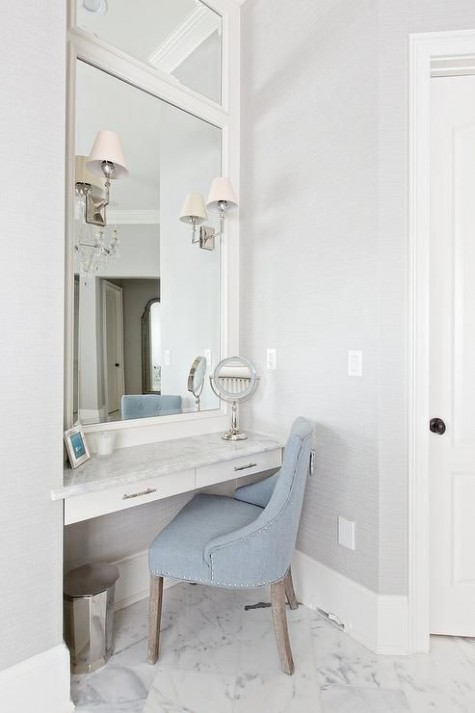 an elegant farmhouse makeup nook with a built-in vanity, powder blue velvet chair, an oversized mirror and several lamps on the mirror