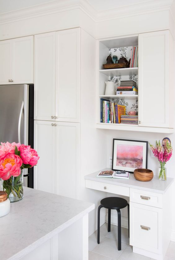 an elegant white kitchen with a small desk and a cabinet over it for storage - both zones look cohesive