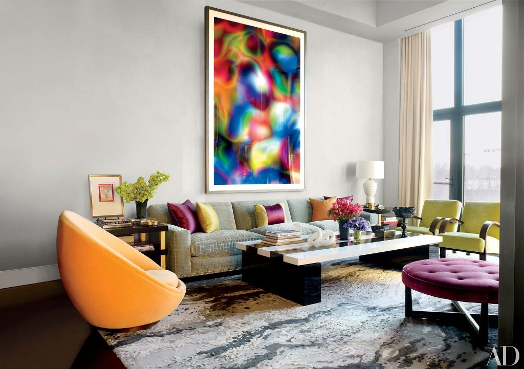 an exquisite living room with a grey sofa, yellow chairs, a purple ottoman, bright pillows and a colorful artwork on the wall