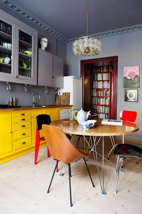 an eye-catchy kitchen with grey upper cabients, matching grey walls and bright yellow lower cabinets that stand out and make the space less moody