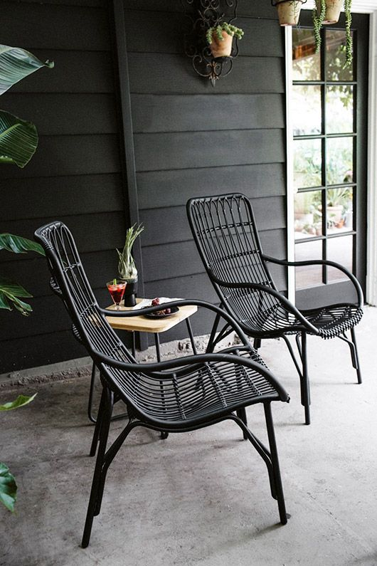 black rattan chairs and a small modern side table of blonde wood for a contrasting Scandinavian space