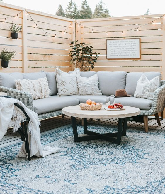 chic modern outdoor furniture with a curved sectional sofa, a rattan chair, a low table and a printed rug is cool
