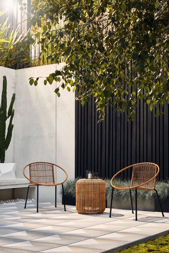 modern rattan chairs and a matching side table with candle lanterns are great for styling a modern patio or terrace