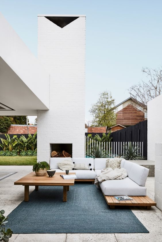 stylish and simple outdoor furniture – a sectional on a wooden frame, a wooden low table and a fireplace clad with white brick