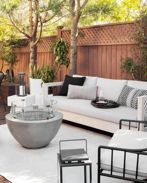 a modern patio with a concrete fire pit