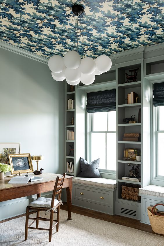 a chic light blue home office with a bold wallpapered ceiling, light blue built-in storage units, a stained desk and a chair