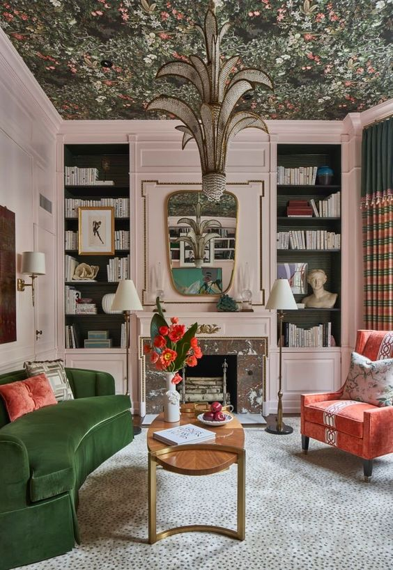 a refined living room with blush walls, a floral wallpaper ceiling, built-in shelves, a green sofa and a coral chair is chic