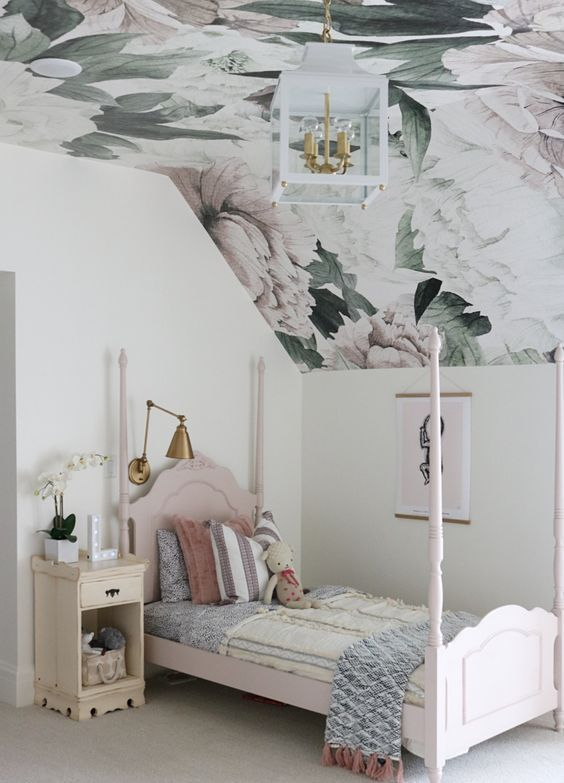 an attic kid's room with a dreamy floral wallpaper ceiling, a pink bed and a vintage nightstand, a pendant lamp and some printed textiles