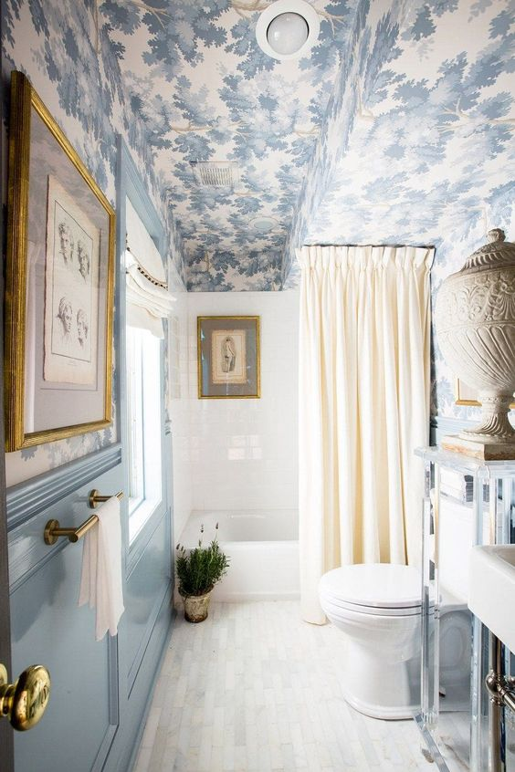 a light blue bathroom with paneled walls, a blue printed wallpaper ceiling, a bathtub, some artworks and potted greenery