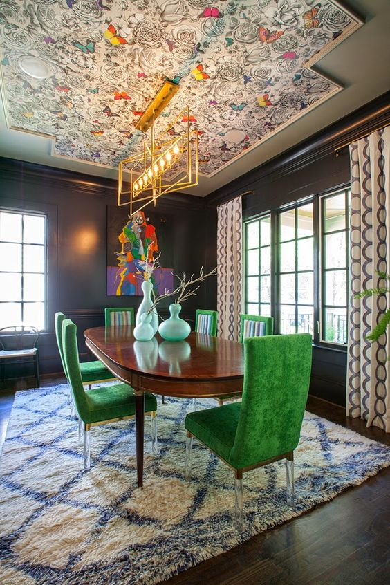 a bright and chic dining room with black walls, a bright butterfly wallpaper ceiling, a stained table and green chairs