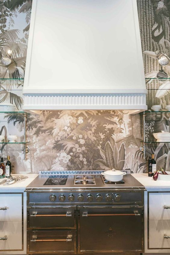 a chic vintage-inspired kitchen with a dreamy printed wallpaper backsplash, a metal cooker and a large white hood
