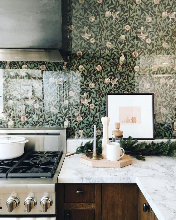 a chic stained kitchen with white stone countertops, a floral wallpaper backsplash covered with glass to save it