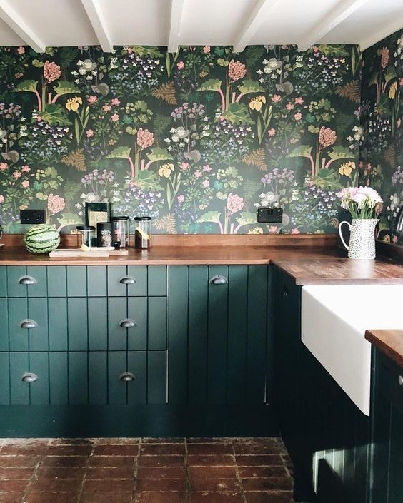 a dark green kitchen with dark floral wallpaper, butcherblock countertops and a simple brick floor is very stylish