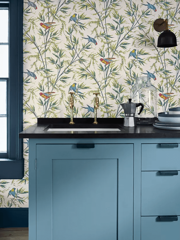 a chic blue kitchen with black stone countertops and botanical and bird printed wallpaper for a backsplash