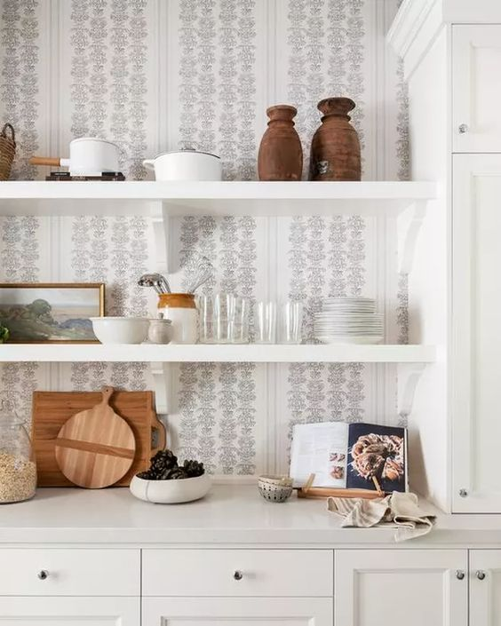 a chic neutral kitchen with white cabinetry, white shelves and a printed wallpaper backsplash is a gorgeous idea