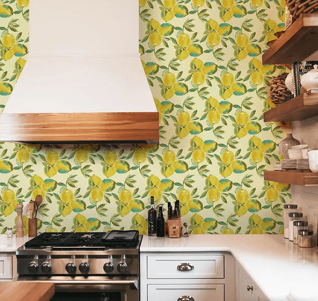 a white kitchen with bright retro wallpaper on the wall, a shelving unit and a large white hood