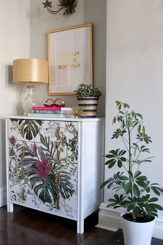 a beautiful chest of drawers covered with pretty tropical wallpaper and with gold knobs is a very refined idea
