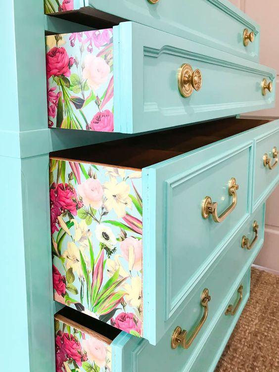 a bright turquoise chest of drawers with brass handles is made cooler with bright tropical wallpaper
